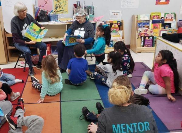 Two adults sitting in chairs in a pre-k classroom reading a book while 3-5 year old children listen while sitting on the rug in front of them.