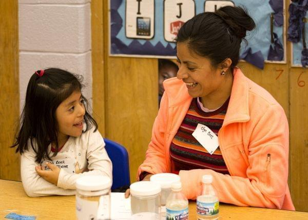 A woman and child are sitting at a table together.  They are smiling at each other.