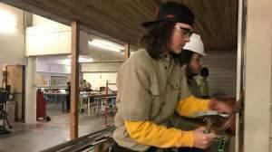 Shelby Landers and Matthew Mangold, both students at Capital Area Career Center, nail siding to the front of the house they're building in the trades class. Landers says he's happy to get out of the classroom and get more handson experience