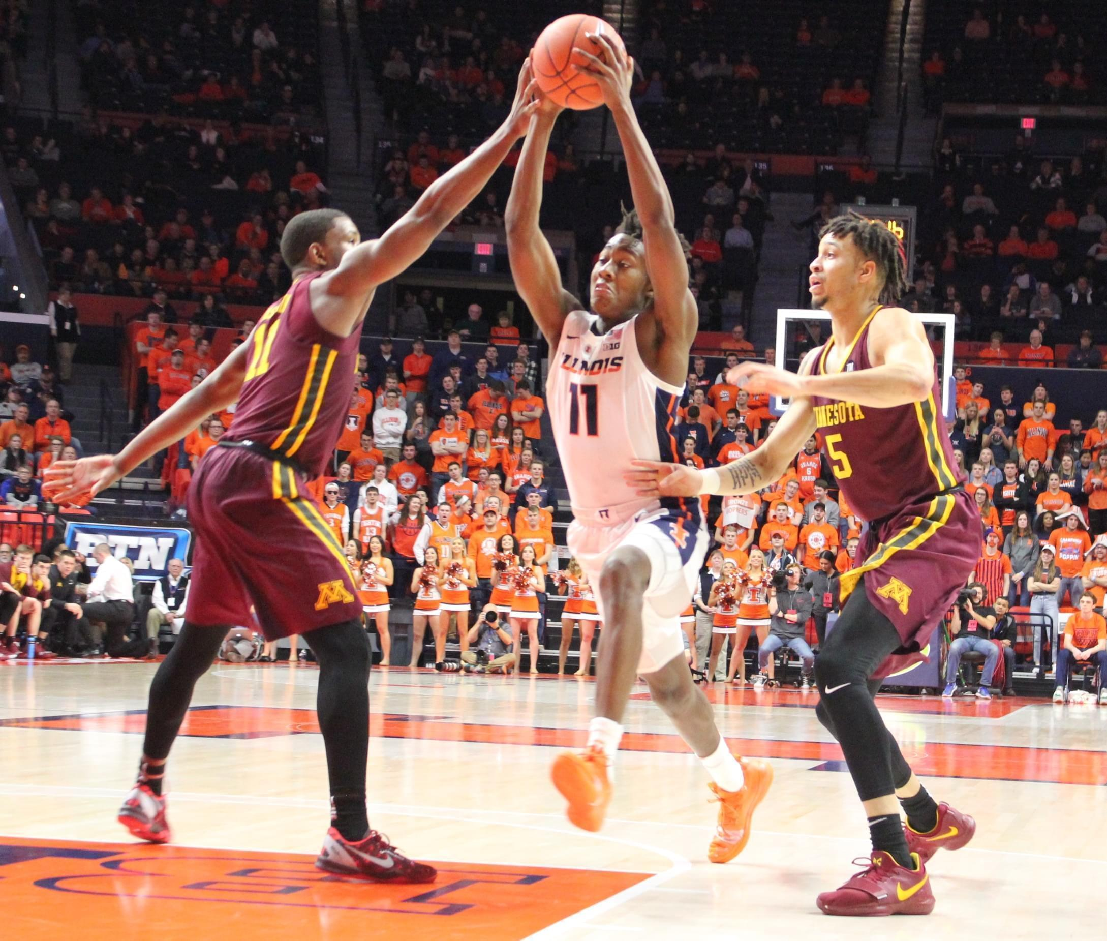 Ayo Dosunmu maneuvers between a pair of Golden Gophers during Illinois' 95-68 win, Wednesday in Champaign.