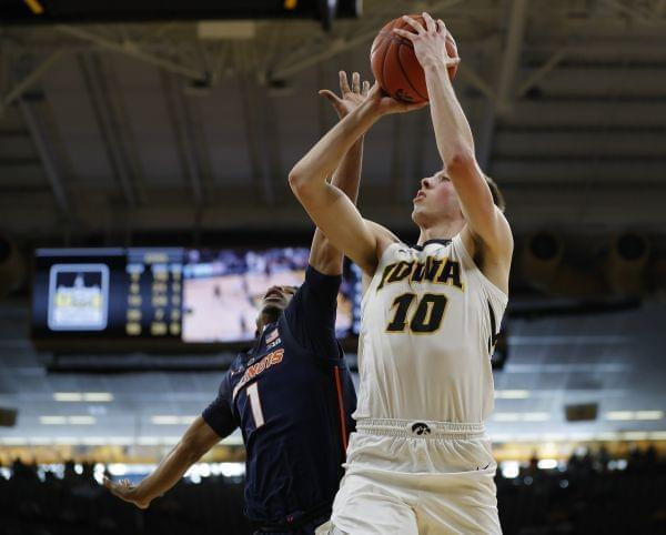 Illinois guard Trent Frazier, left, tries to defend against a shot by Iowa guard Joe Wieskamp, right, during the second half of an NCAA college basketball game, Sunday, Jan. 20, 2019, in Iowa City.