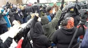 """People praying at the Pratt Co. in Aurora Sunday to cleanse the site of the """"defilement"""" of Friday's mass shooting."""
