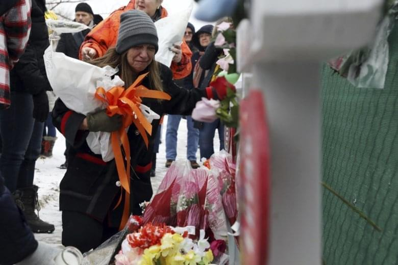 People pray at a makeshift memorial Sunday, Feb. 17, 2019, in Aurora, Ill., near Henry Pratt Co. manufacturing company where several were killed on Friday. Authorities say an initial background check five years ago failed to flag an out-of-state felo