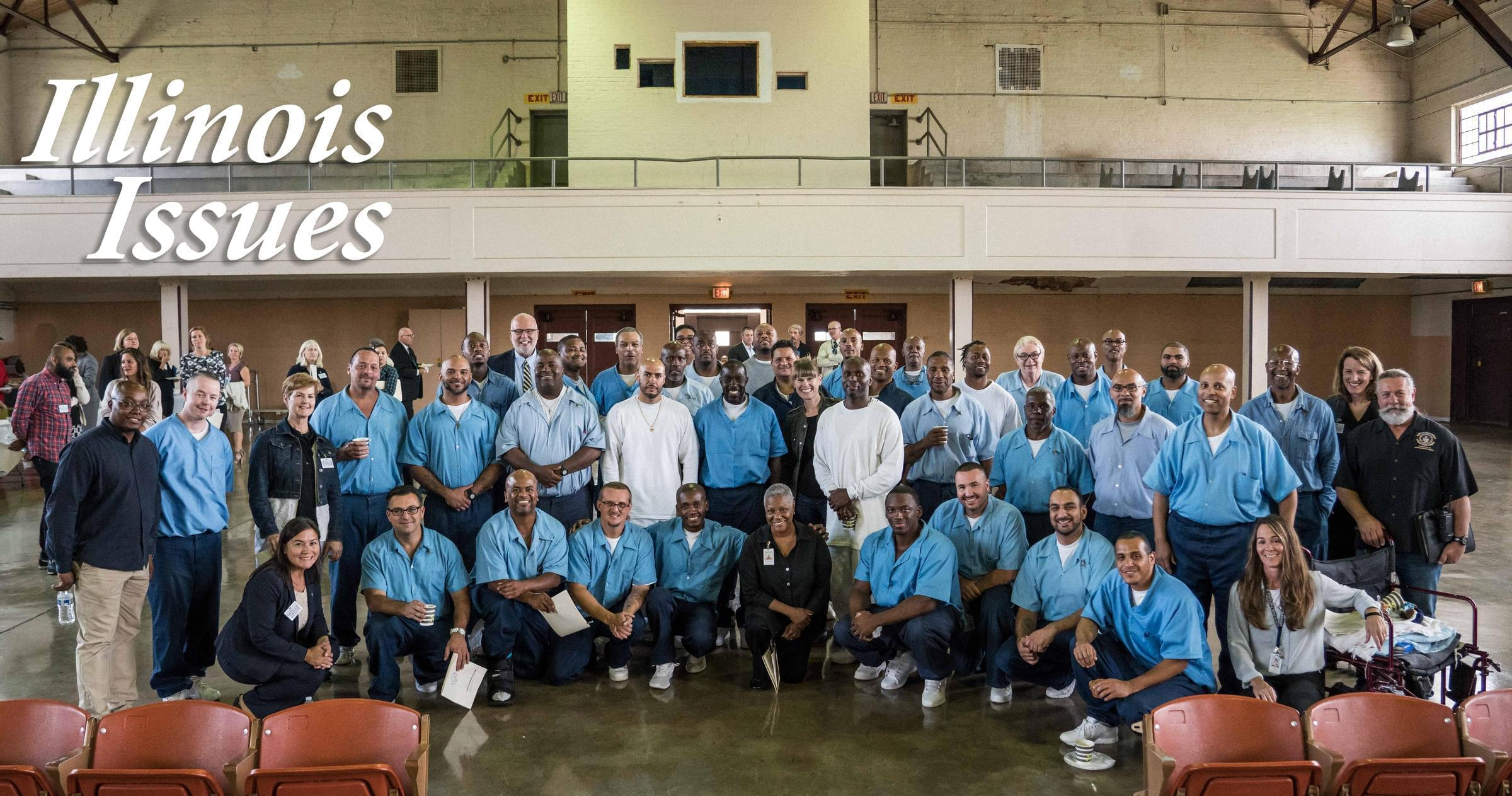 Students, teachers, staff and volunteers posed for a picture after a convocation ceremony for the fall semester of a masters degree program at Stateville Correctional Center.