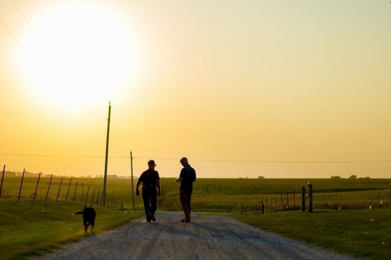 Two men and a dog in a farm driveway.