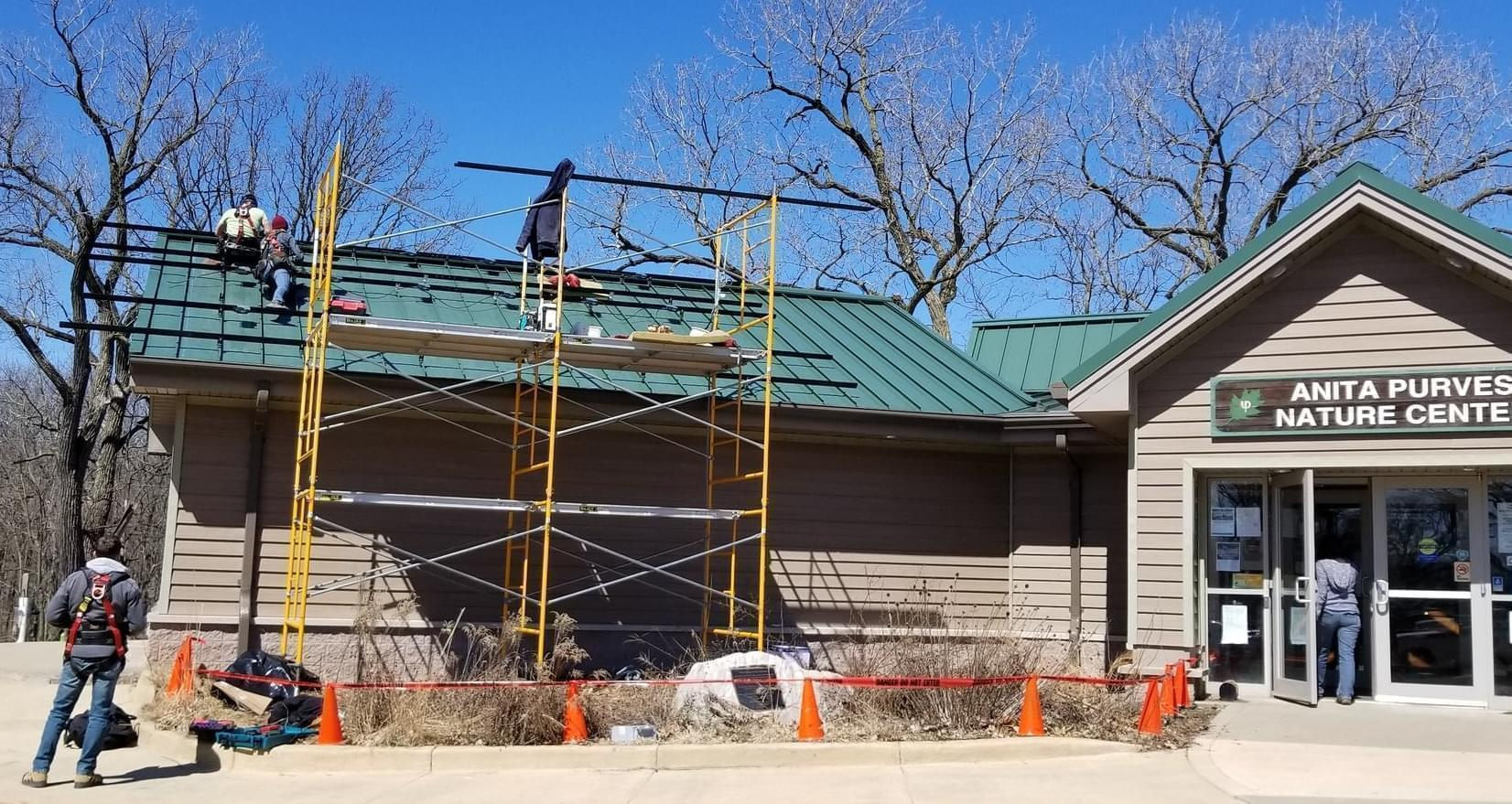 Workers install solar panels on the roof of the Anita Purves Nature Center, at Crystal Lake Park in Urbana.