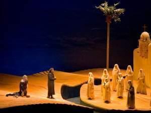 people perform on a desert scene on stage