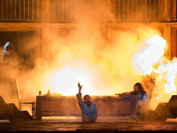 stage burns while two people perform