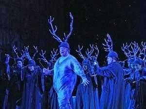 people perform in antlers on stage