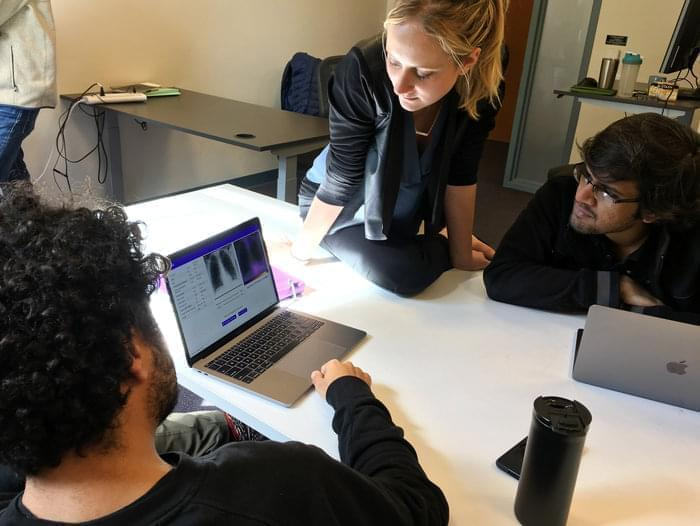Amir Kiani (from left), Chloe O'Connell and Nishit Asnani troubleshoot an algorithm to diagnose tuberculosis in computer lab at Stanford University.