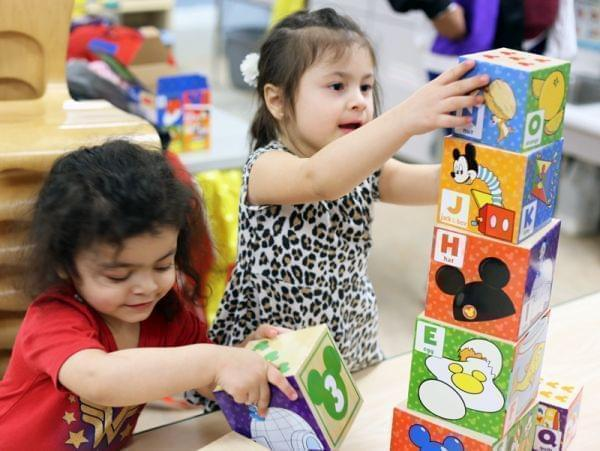 Two 3-year-old children use their hands to build a tower using cardboard nesting blocks.