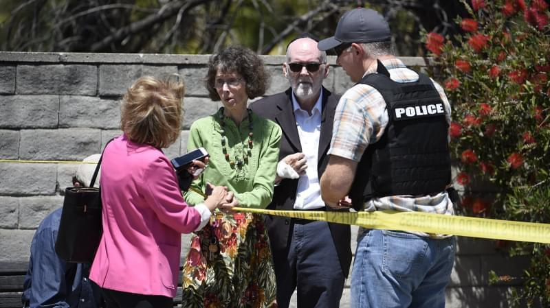 Synagogue members stand behind police tape talking to a deputy from the San Diego County Sheriff's department.