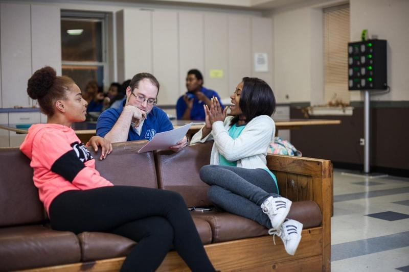 An employee at the Night Ministry talks with two residents of the program while they sit on a couch in a meeting room.