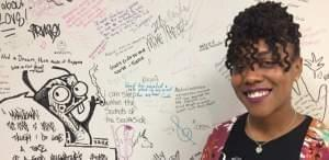 Tiffany Reynolds stands by a testimony wall at her Pilsen business, Soul and Wellness.