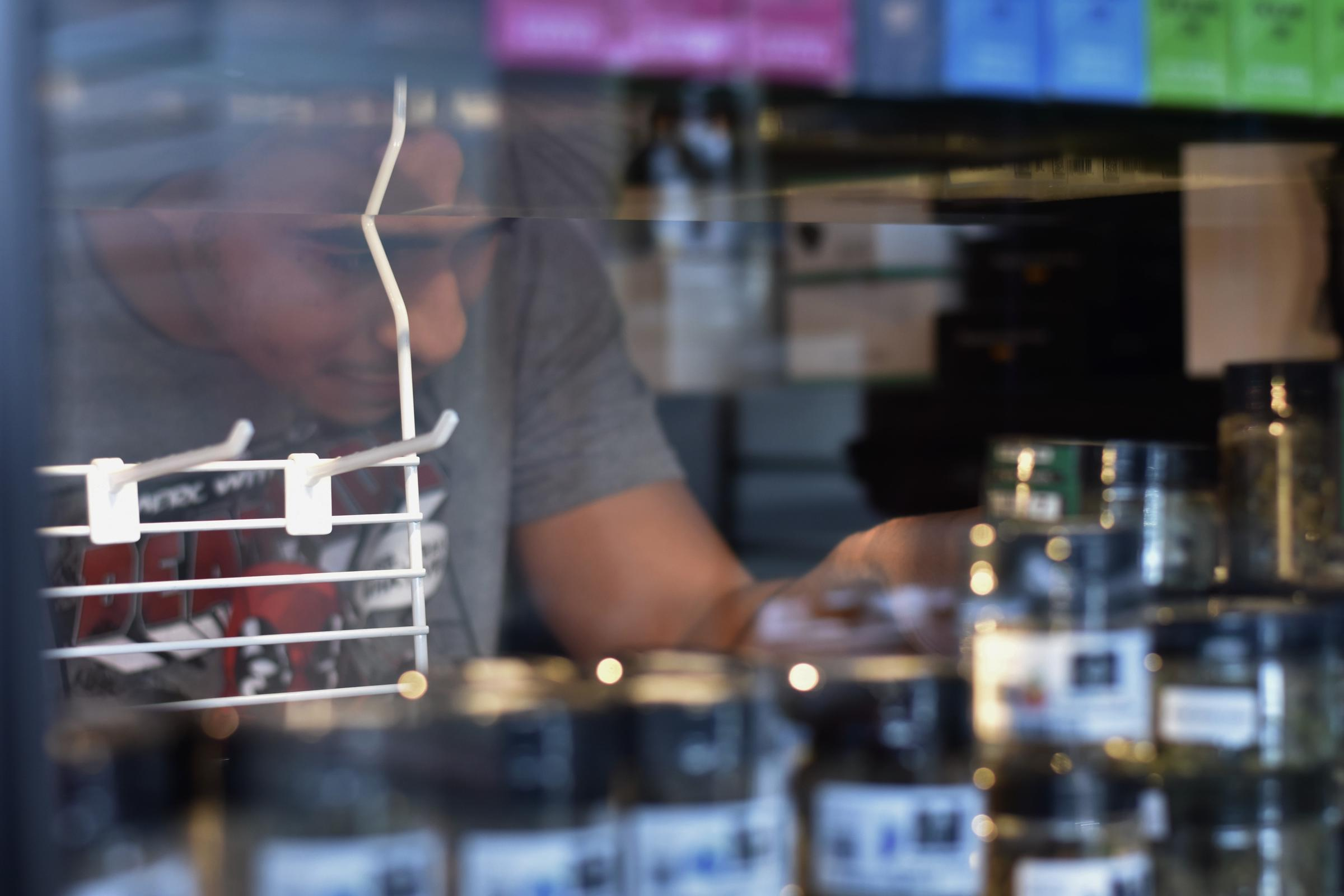 Logan Chase arranges CBD products in a glass case display.