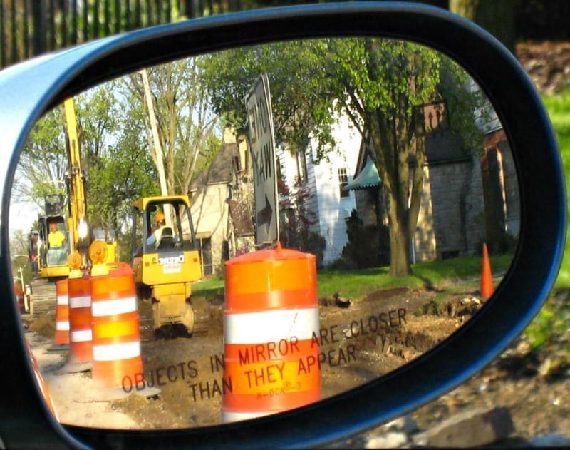 A roadside construction crew, seen through a rearview mirror.