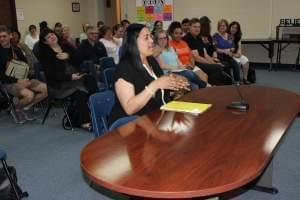 Jennifer Ivory-Tatum behind a desk speaking to the Urbana District 116 School Board with meeting attendees seated behind her.