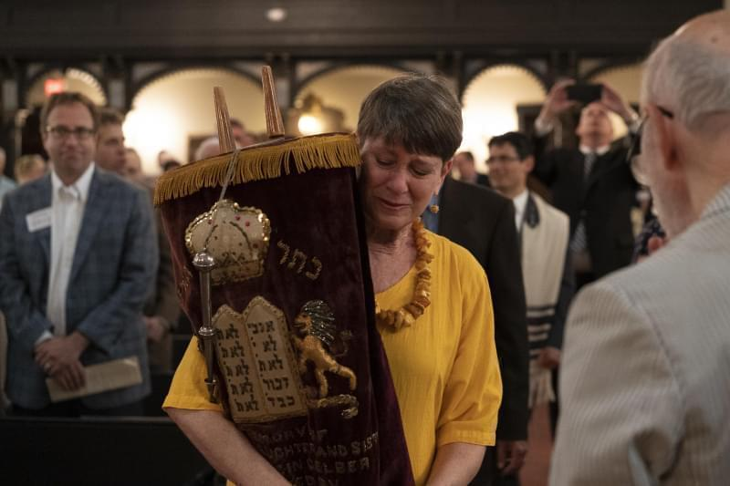 B'nai Sholom congregant Carla Gordon carries one of the sacred Torah scrolls through the synagogue during Saturday's deconsecration ceremony. The nearly 150-year-old synagogue closed its doors due to low membership and financial hardship.