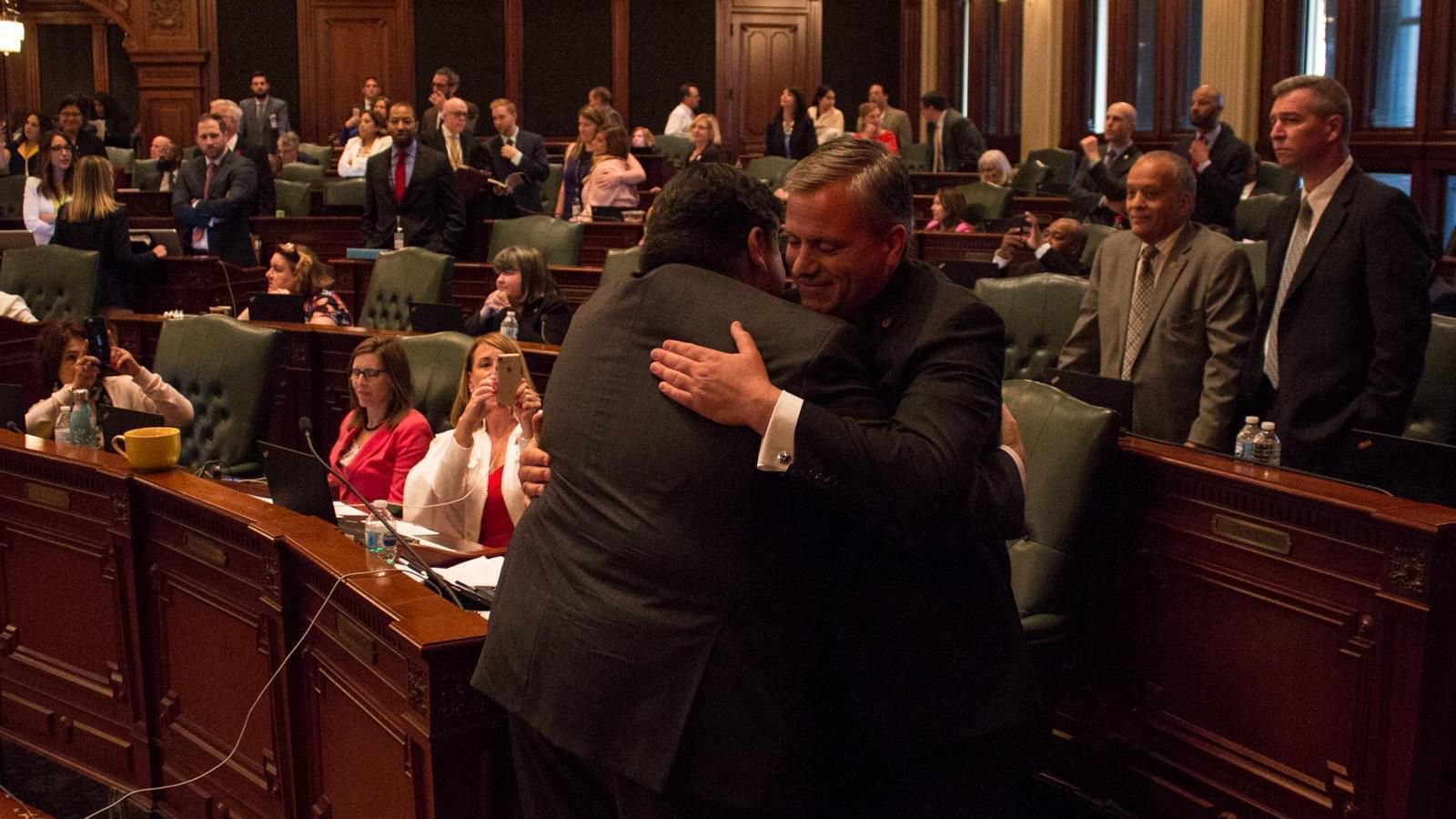 Gov. J.B. Pritzker, left, hugs state Rep. Robert Martwick after passage of a constitutional amendment to allow for a graduated income tax in Illinois.