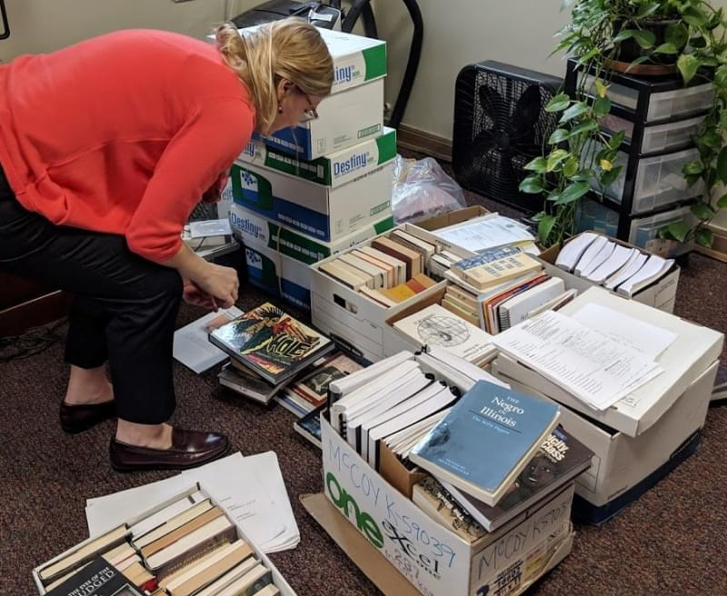 Holly Clingan crouches down to look through boxes of books removed from the EJP library at the Danville Correctional Center in an office on the University of Illinois campus.