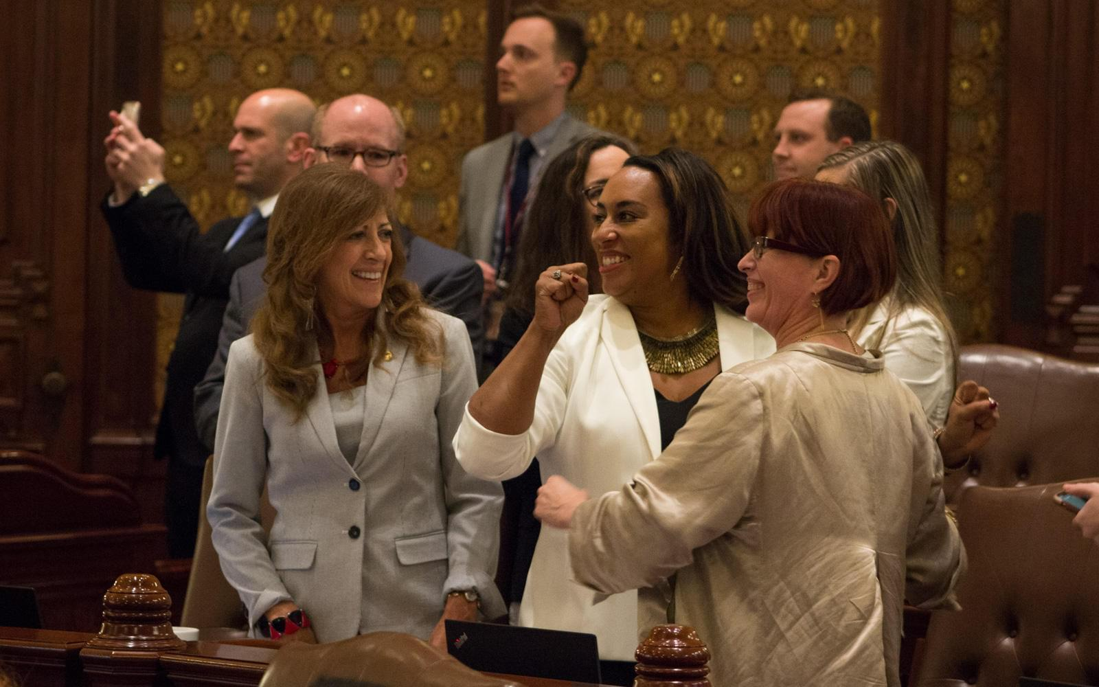 Illinois state Senators celebrate the passage of legislation to legalize marijuana. The lead sponsors were Sens. Heather Steans, right, and Toi Hutchinson, center.