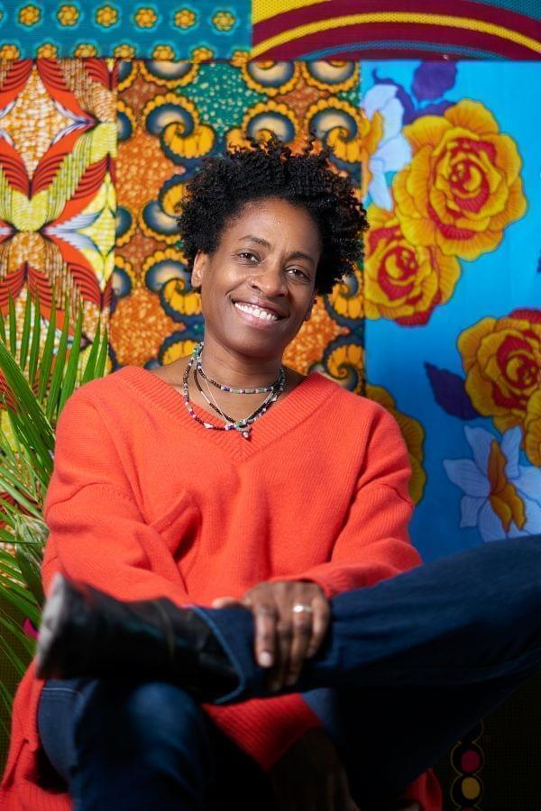 Jacqueline Woodson smiling and posing in front of a colorful background.
