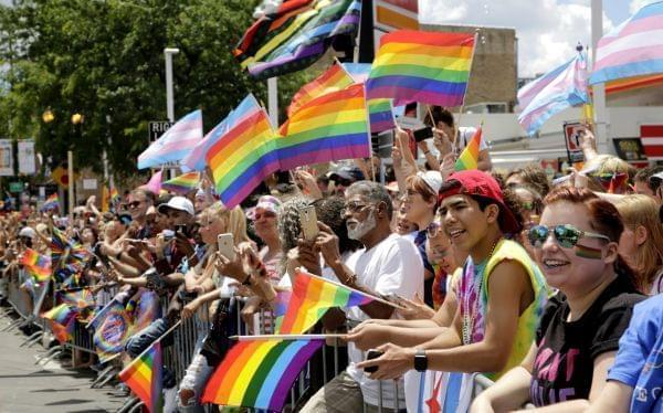 A crowd holds rainbow flags as they watch the 48th Annual Chicago Pride Parade on Sunday, June 25, 2017 in Chicago.