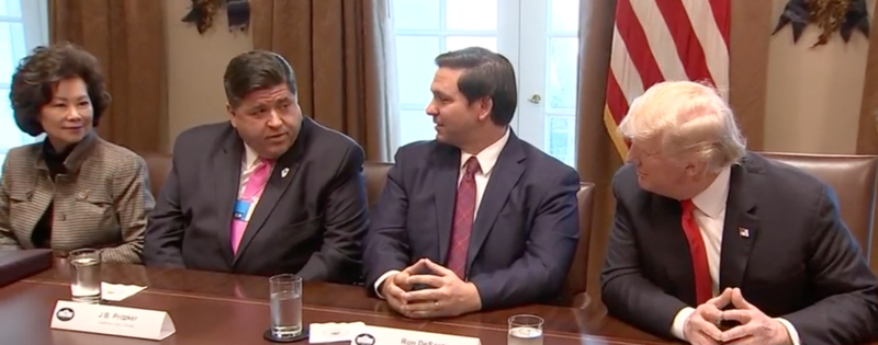 J.B. Pritzker and others seated at a table with President Donald Trump in the White House