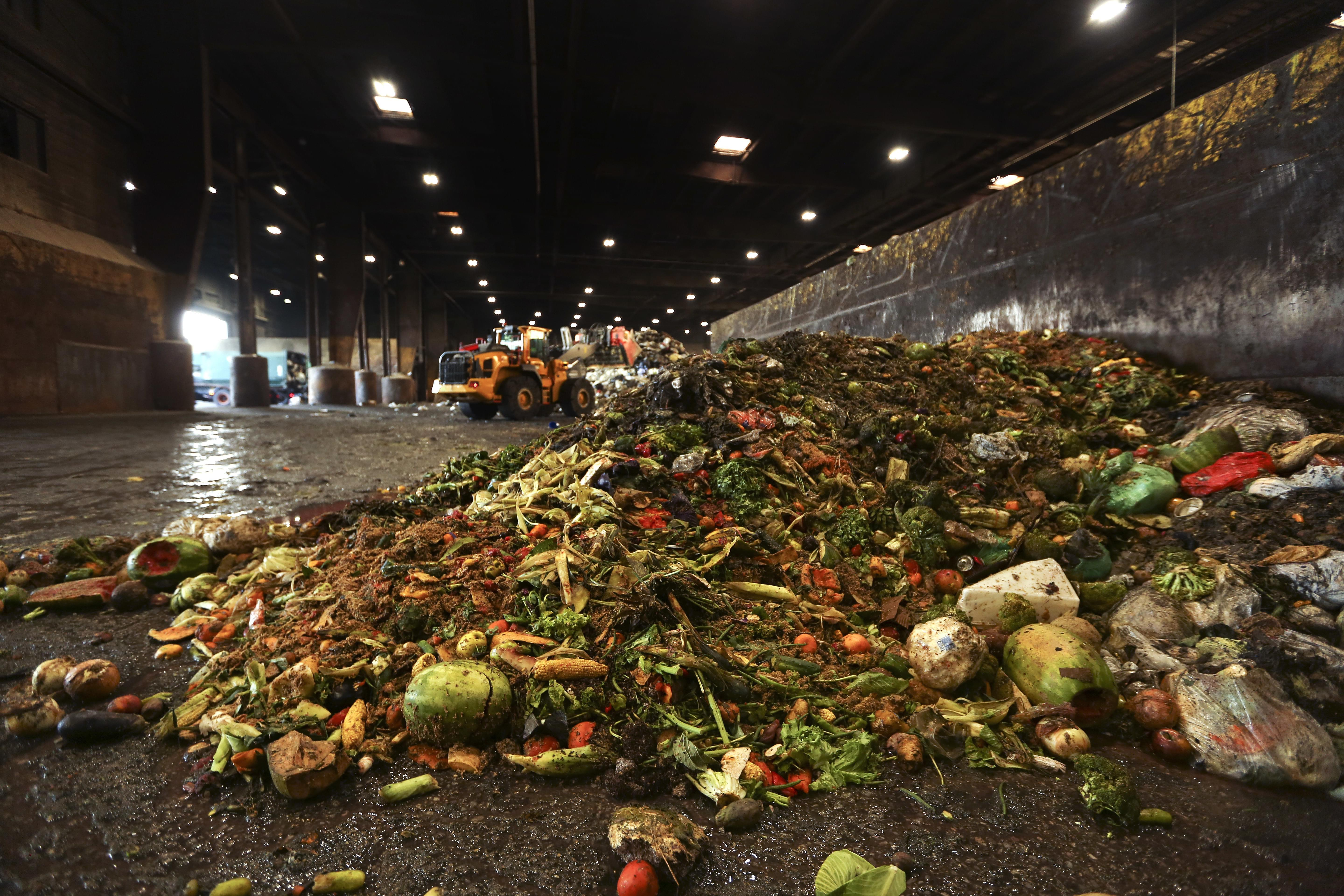 """In this Aug. 29, 2018, photo, at the Waste Management facility in North Brooklyn, tons of leftover food sits piled up before being processed into """"bio-slurry,"""" in New York."""