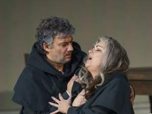 Man and woman embrace on stage.