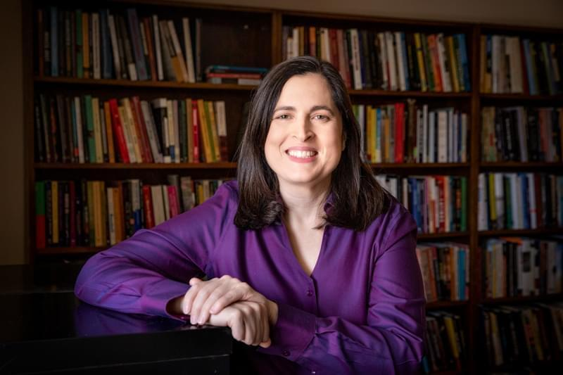 Julie Dowling smiling and sitting in front of several rows of bookshelves