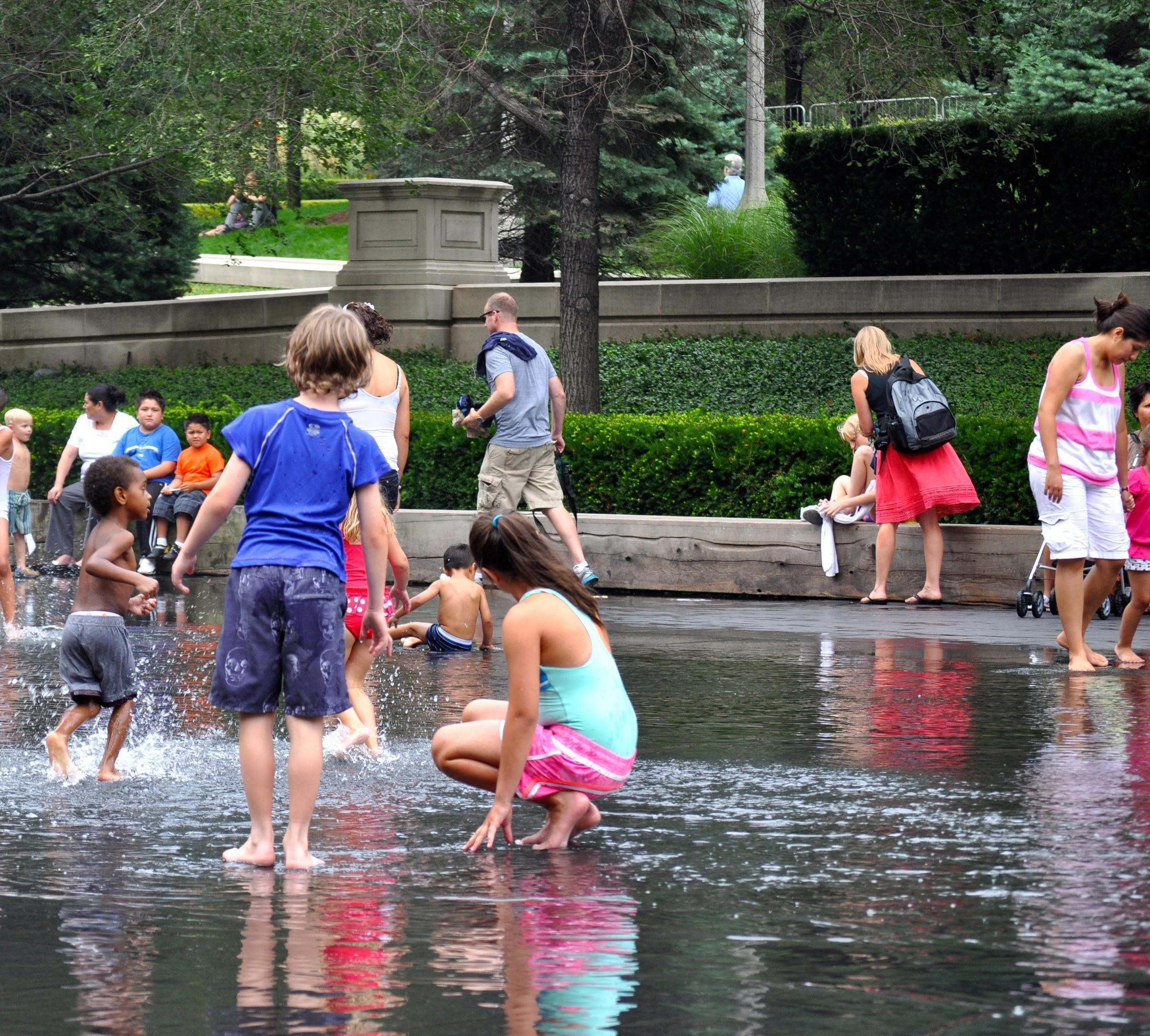 People playing in a fountain during hot weather.
