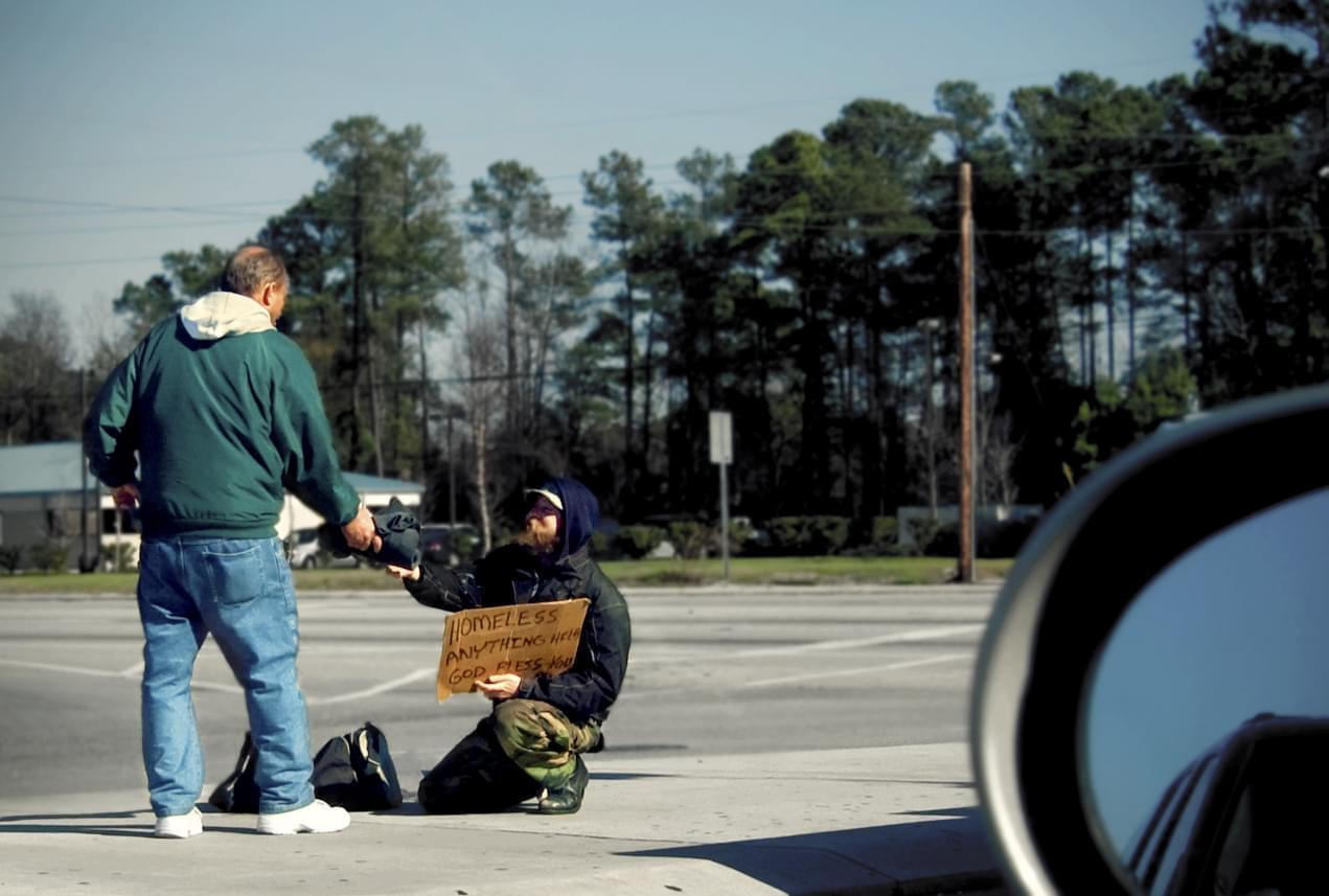 A man asks for money using a cardboard sign that says he is homeless. Another man hands him money while walking by.