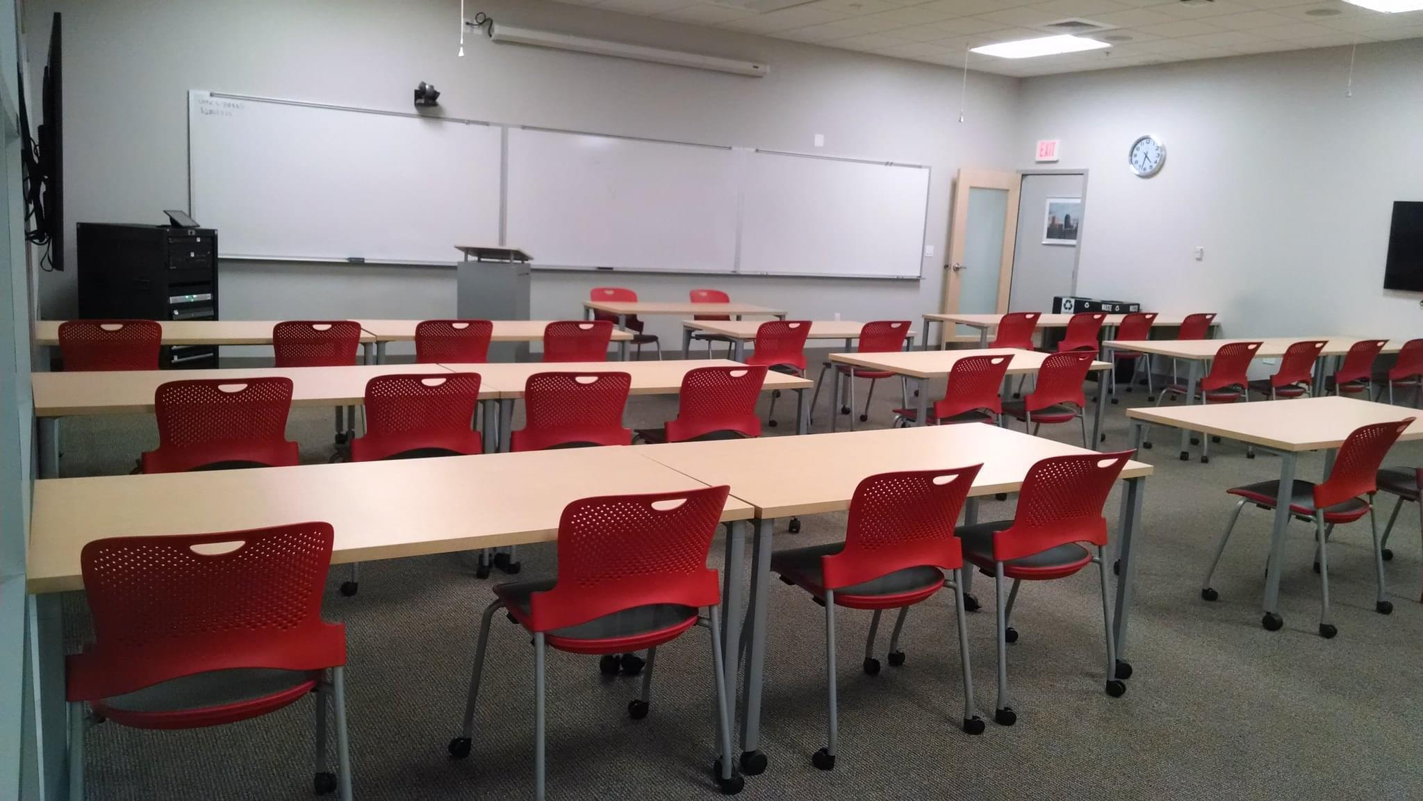 an empty classroom with red chairs