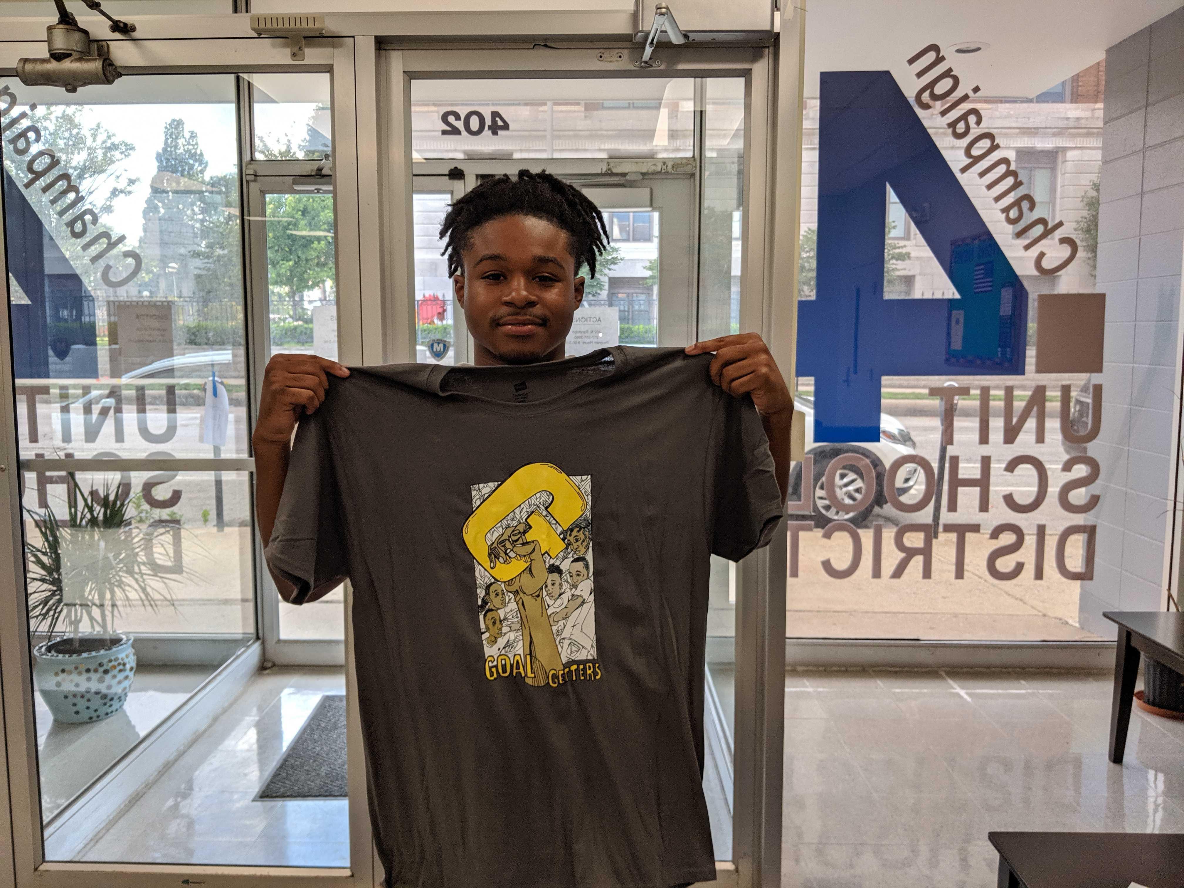 Mekel Brown inside a Unit 4 building holding up a Goal Getter T shirt.