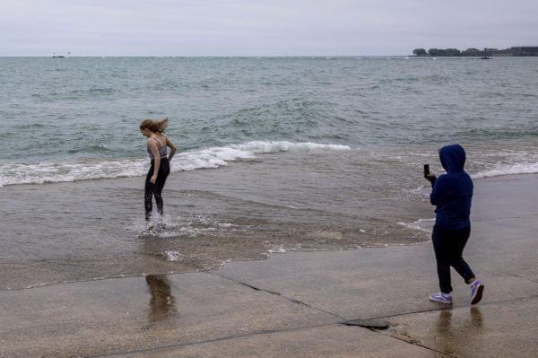 A woman jumps into the shallow water of Lake Michigan as her companion takes her picture at Chicago's Oak Street Beach, Thursday, June 20, 2019.