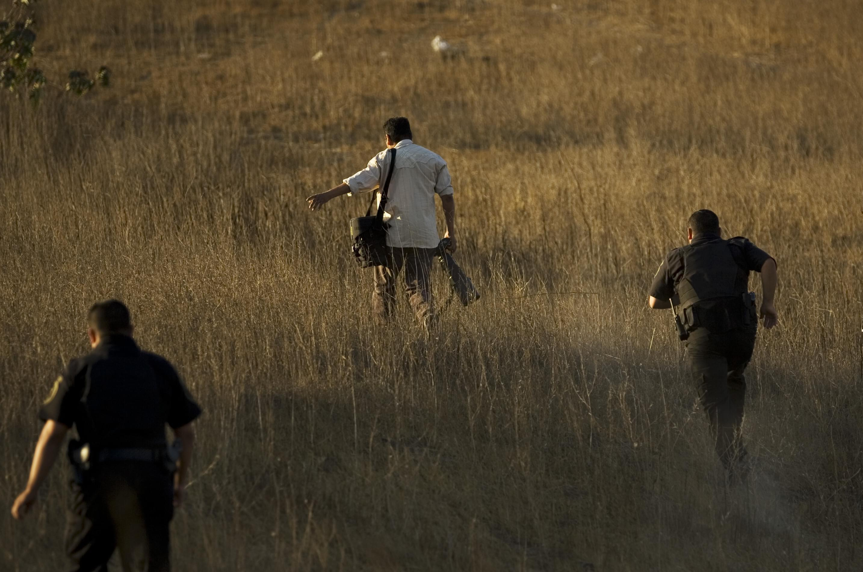 Police officers run after a photographer trying to reach a better view of a crime scene where a police officer was killed in Rosarito, Mexico, Thursday, Oct. 23, 2008.