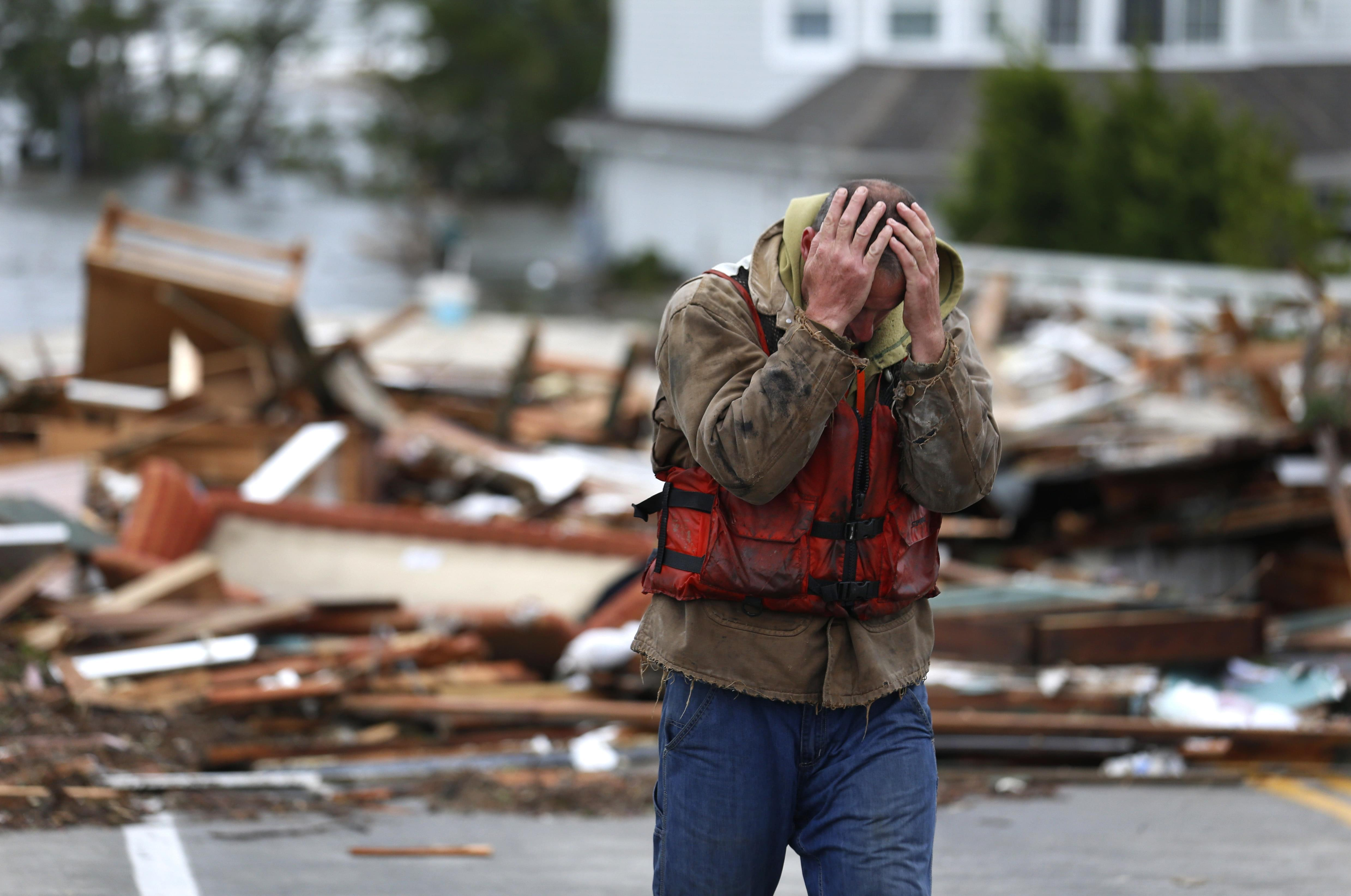 Brian Hajeski, 41, of Brick, N.J., reacts after looking at debris of a home that washed up on to the Mantoloking Bridge the morning after superstorm Sandy rolled through, Tuesday, Oct. 30, 2012, in Mantoloking, N.J.