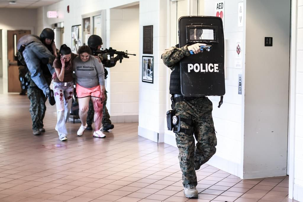"""police officers lead """"victims"""" through a hallway during an active shooter drill"""