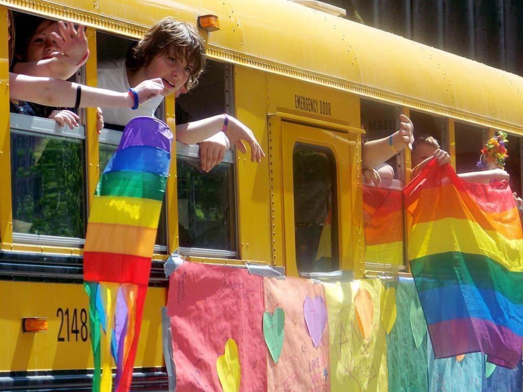 Students leaning out of school bus window with rainbow flags