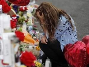 A woman grieves with her head in her hands over a makeshift memorial.