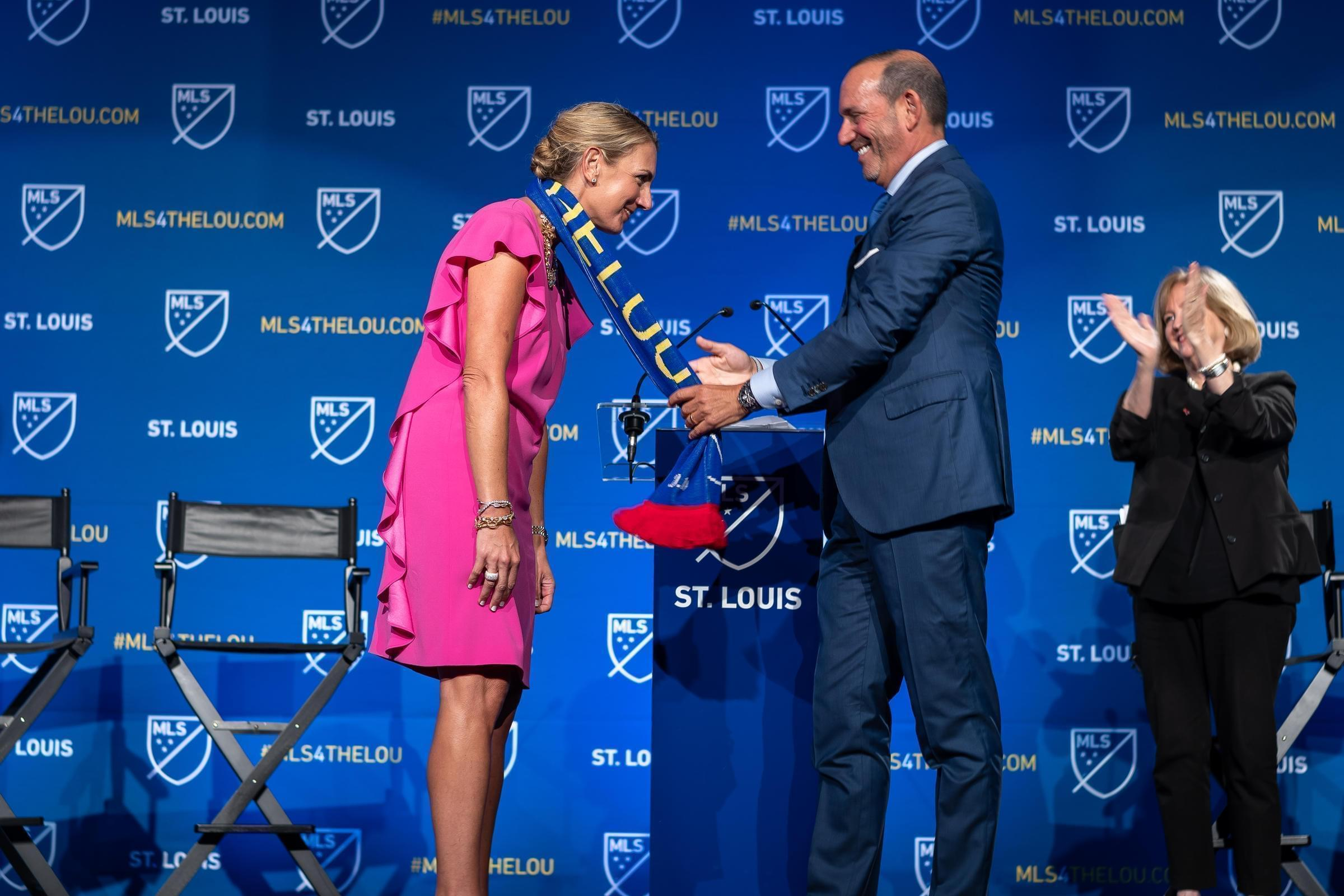 """Major League Soccer Commissioner Don Garber drapes an MLS scarf that reads """"St. Louis"""" over Carolyn Kindle Betz, who leads the ownership group for St. Louis' new professional soccer team."""