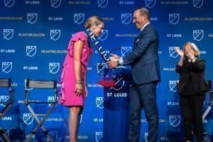 "Major League Soccer Commissioner Don Garber drapes an MLS scarf that reads ""St. Louis"" over Carolyn Kindle Betz, who leads the ownership group for St. Louis' new professional soccer team."