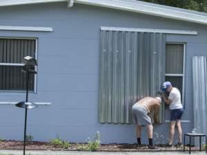 People in Vero Beach, Fla., install shutters on their home on Thursday in preparation for Hurricane Dorian, now expected to be a Category 4 storm when it hits the U.S. coastline.