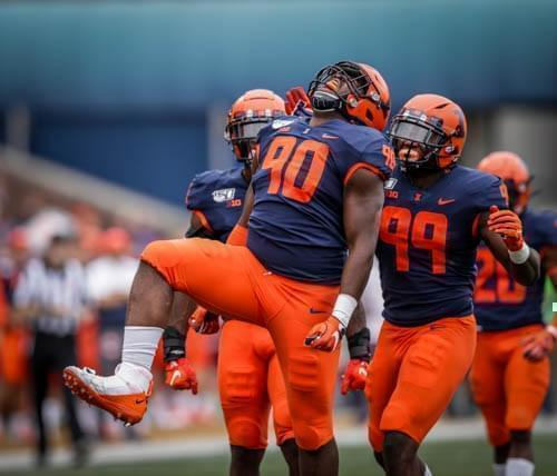 Illinois' Lere Oladipo celebrates after a sack with teammate Owen Carney during the Illini's 42-3 win over Akron.