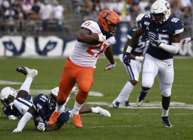 Illinois running back Ra'Von Bonner breaks free of Connecticut linebacker D.J. Morgan and runs in for a touchdown during the first half of an NCAA college football game, Saturday, Sept. 7, 2019, in East Hartford, Conn.