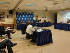 Champaign Police Chief Anthony Cobb and Champaign Unit 4 Director of Achievement and Student Services seated at a table in front of microphones with Unit 4 staff seated around them.