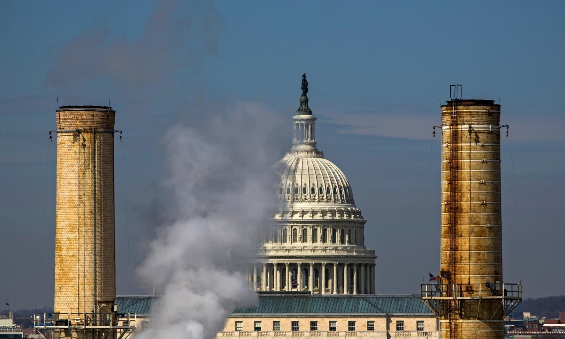 The dome of the US Capitol is seen behind the smokestacks of the Capitol Power Plant, a coal-burning plant in Washington DC.