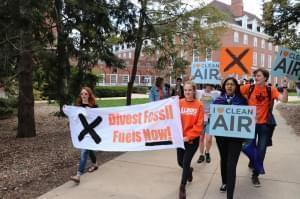 college students holding environmental protest signs march on the campus quad