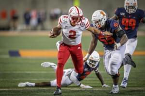 Nebraska quarterback Adrian Martinez runs toward the end zone with Illinois' Jamal Milan and Owen Carney in pursuit.